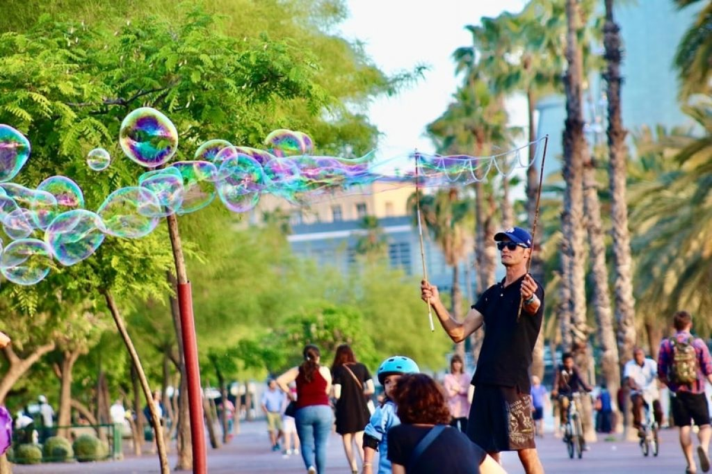 man-playing-with-bubbles-in-park-barcelona