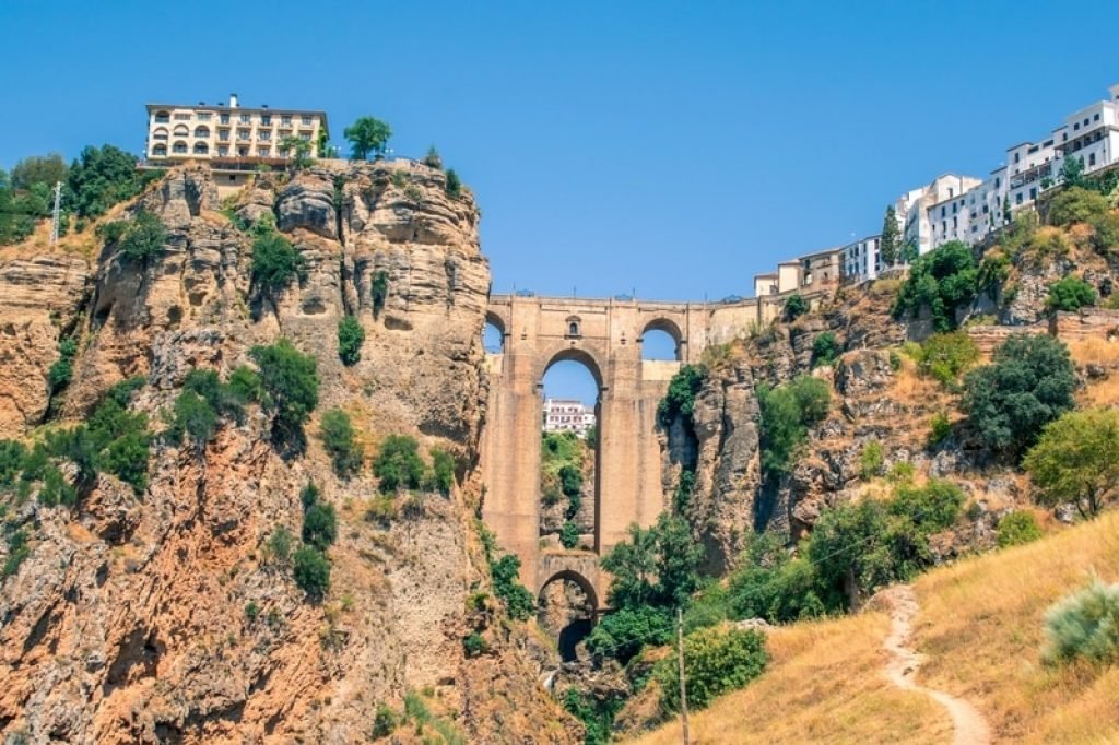 spanish city and bridge over deep gorge in mountains