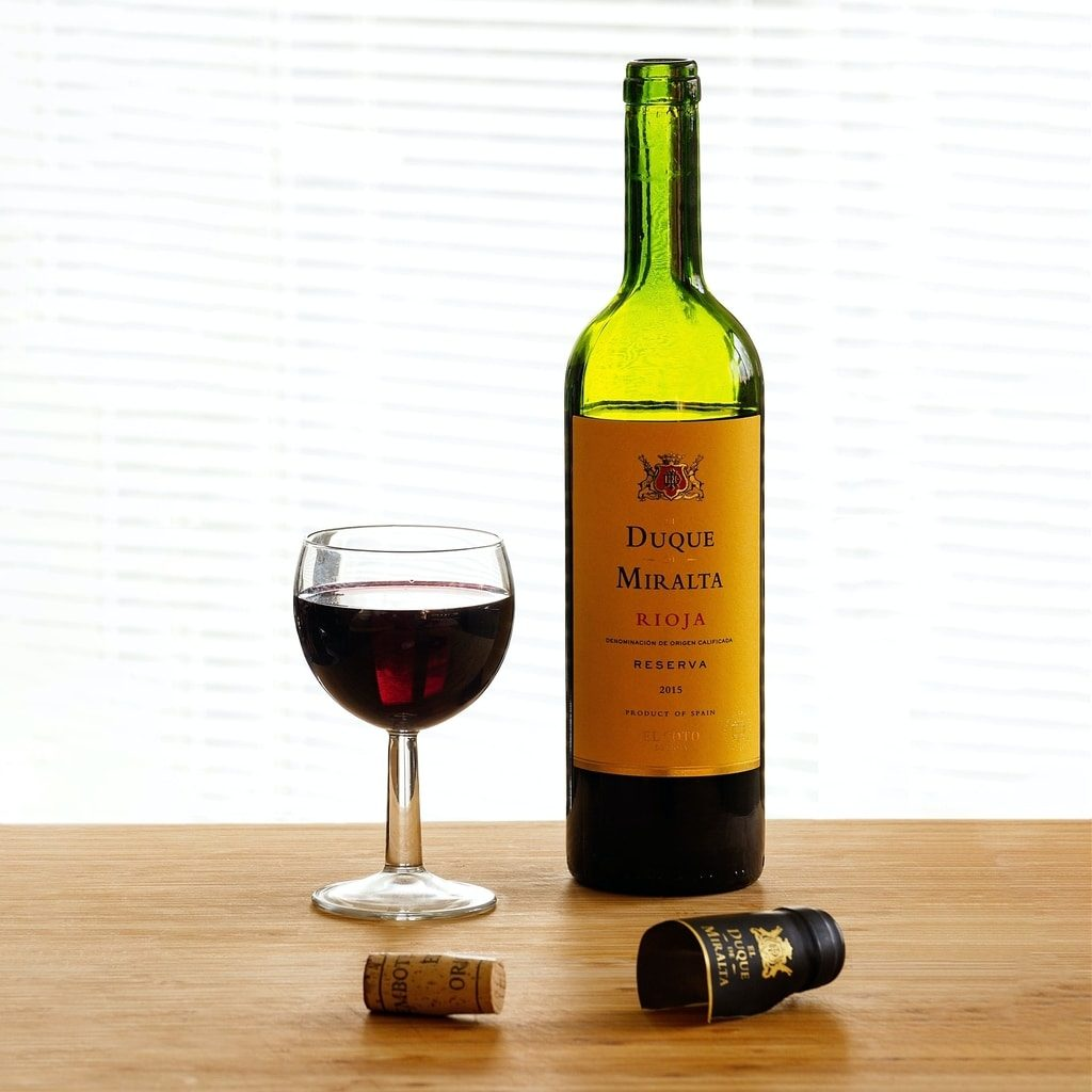 opened-bottle-of-rioja-red- duque-miralta-with-a-glass-of-wine-standing-next-to-it
