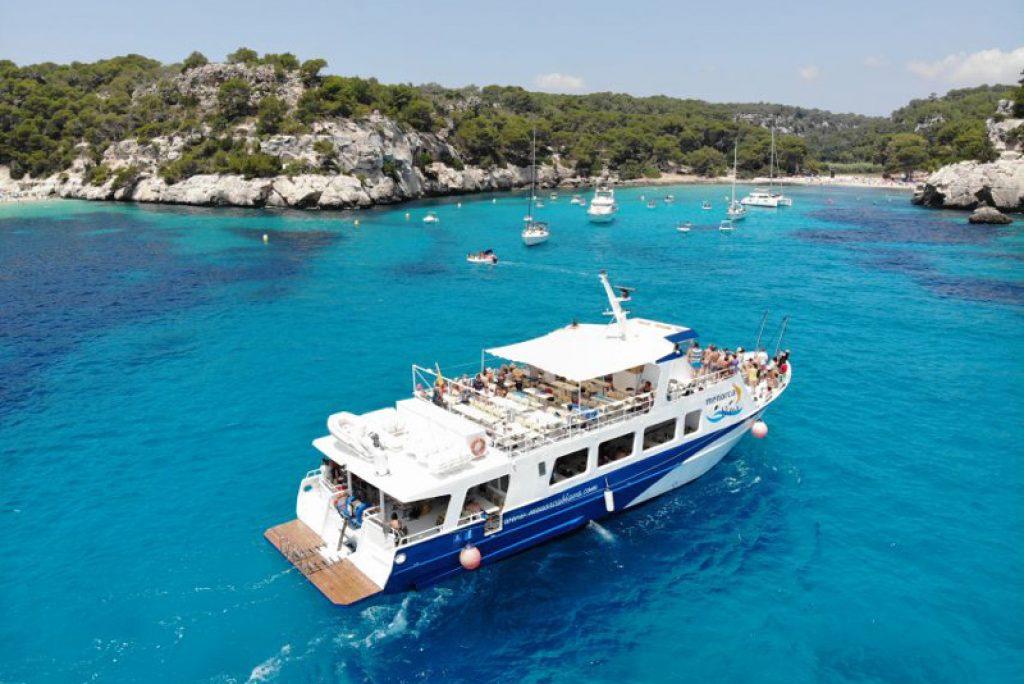 cruise boat in blue water menorca bay